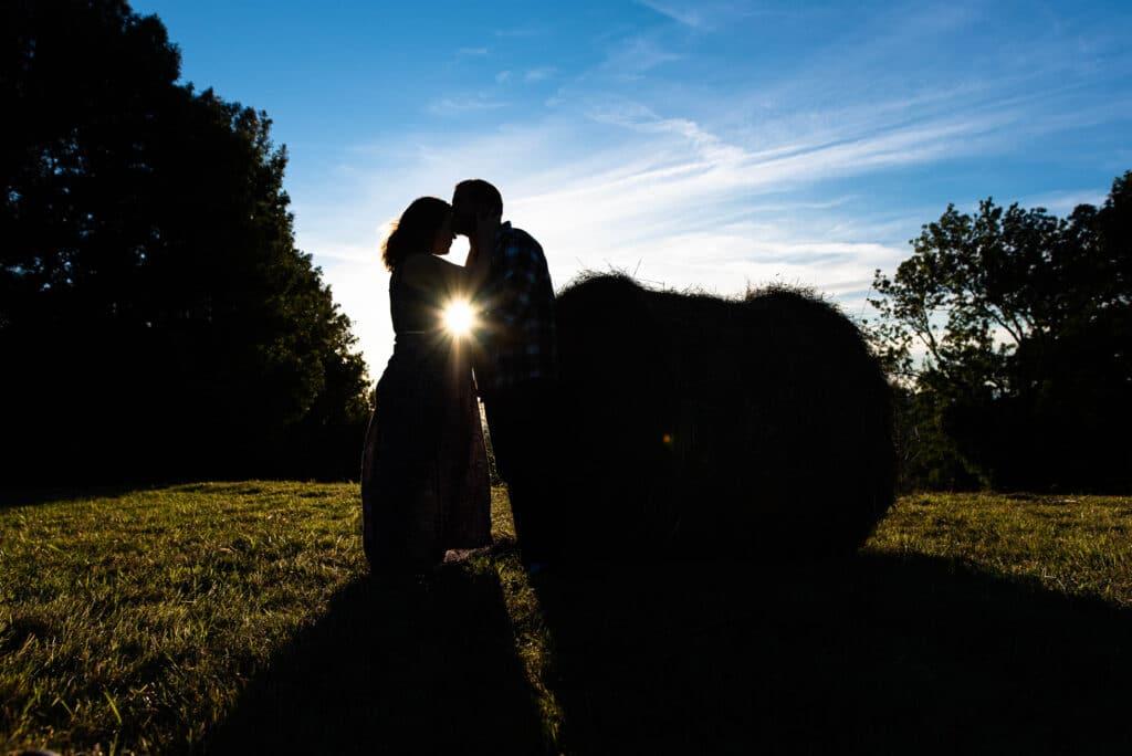 Fin de séance grossesse devant le soleil couchant dans les champs