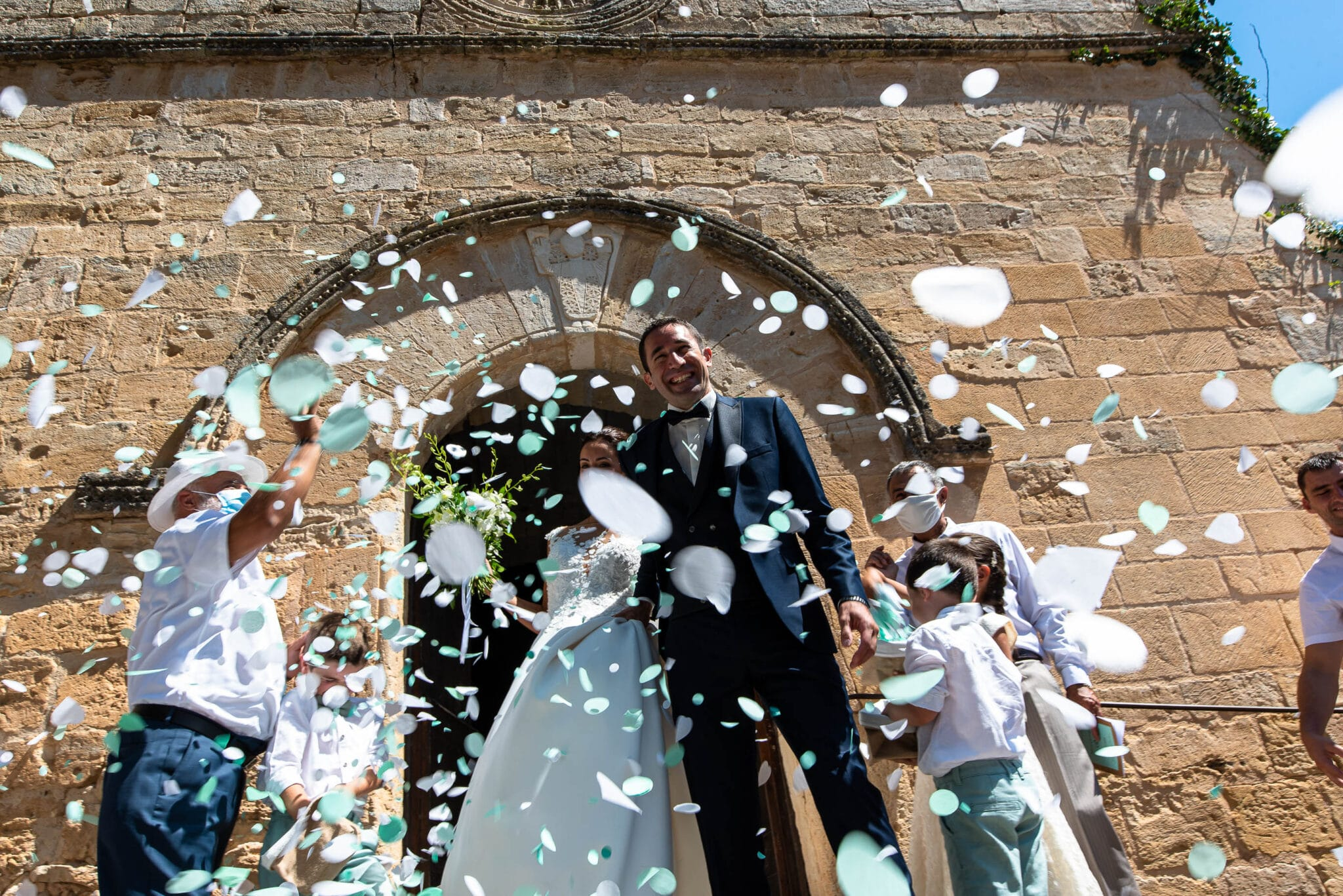 The bride and groom surrounded by green and white petals in front of the church