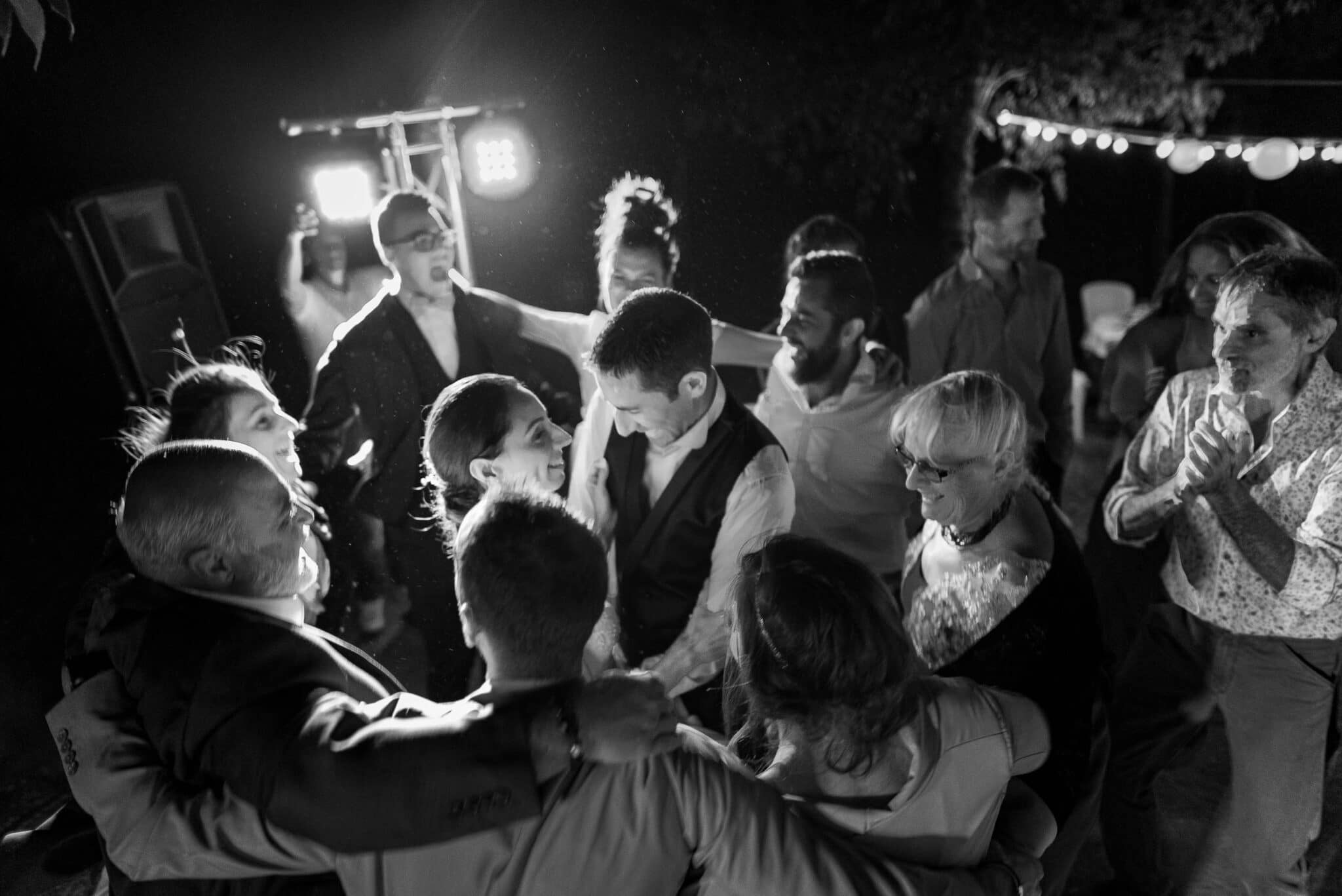 The bride and groom and guests dance